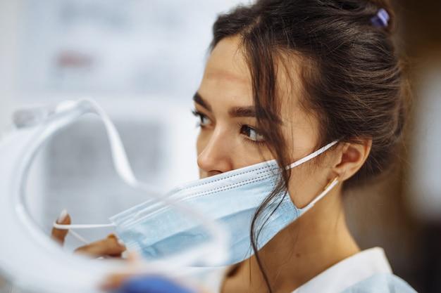 Infermiera stanca si toglie una visiera protettiva e una mascherina medica dopo un duro turno di lavoro in ospedale. la dottoressa combatte la pandemia di coronavirus lavorando sodo e stremata