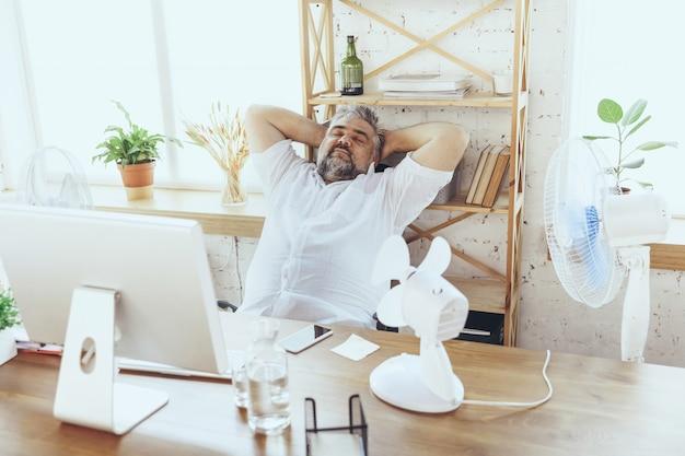Stanco. uomo d'affari, manager in ufficio con computer e ventola che si raffredda, si sente caldo, arrossato. usando la ventola ma soffrendo ancora del clima scomodo nell'armadio. estate, lavoro d'ufficio, affari.