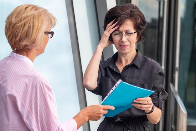 Donna di affari sovraccaricata stanca con i documenti
