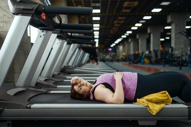 Stanco donna sovrappeso sdraiato sul tapis roulant in palestra, tempo libero dopo l'allenamento attivo. persona di sesso femminile obesa lotta con l'eccesso di peso, allenamento aerobico contro l'obesità, club sportivo