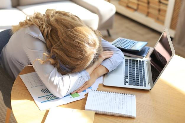 Donna oberata di lavoro stanca che riposa mentre stava lavorando al computer portatile.