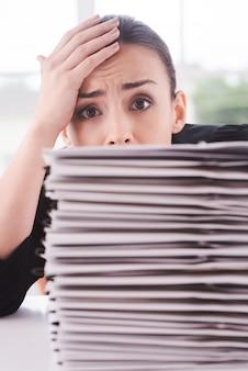 Stanco delle scartoffie. giovane donna depressa in tuta che guarda fuori dalla pila di documenti che giace sul tavolo e si tocca la fronte con la mano