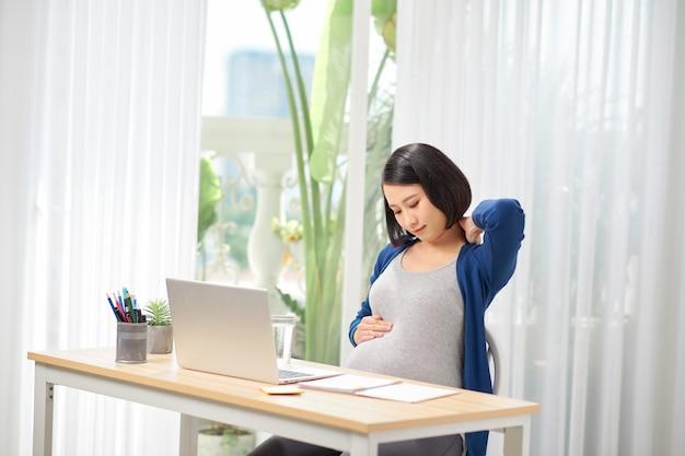 Donna incinta stanca. donna incinta che tiene il collo in ufficio a casa.