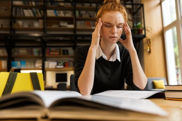 Adolescente dai capelli rosso stanco che studia al tavolo
