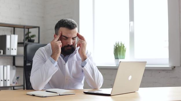Medico maschio remoto stanco seduto vicino al computer portatile in studio medico e soffre di mal di testa.