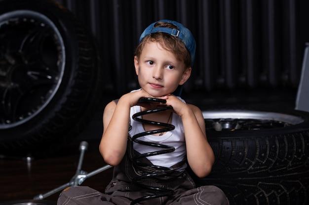 Bambino triste stanco nel garage tra le gomme e le ruote che tengono un ammortizzatore a molla