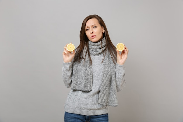 Stanco triste giovane donna in maglione grigio, sciarpa tenere i limoni isolati su sfondo grigio muro, ritratto in studio. stile di vita sano, persone sincere emozioni, concetto di stagione fredda. mock up copia spazio.