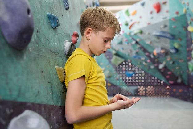 Giovane stanco o triste in maglietta gialla che si appoggia contro l'attrezzatura da arrampicata e che guarda le sue mani durante la pausa