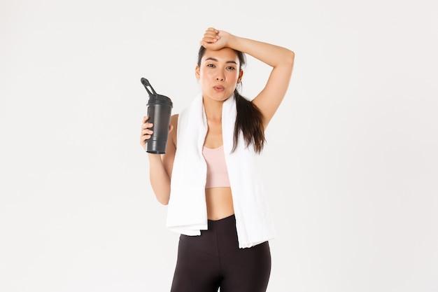 Ragazza asiatica stanca ma soddisfatta che si asciuga il sudore dalla fronte ed espira dopo un buon allenamento, bere acqua o proteine durante la sessione di allenamento.