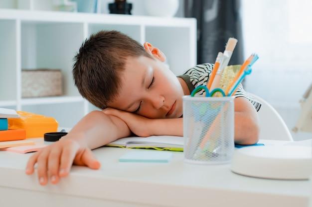 Scolaro stanco che dorme sul suo tavolo dopo aver completato un compito scolastico a casa. ritorno a scuola, difficoltà di apprendimento.