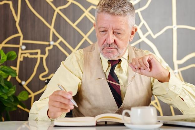 Uomo d'affari senior stanco che toglie gli occhiali e scrive nel pianificatore i suoi pensieri e le sue idee