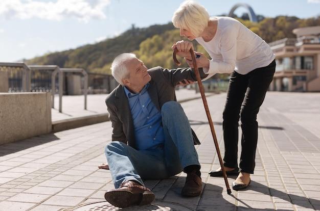 Pensionato di bell'aspetto senior stanco che tiene il bastone in mano e sorride mentre la signora piacevole chiede aiuto