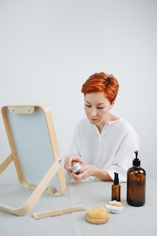 Donna stanca dai capelli corti che apre una lattina di correttore, seduta davanti allo specchio. utilizzo di prodotti e cose eco-compatibili.