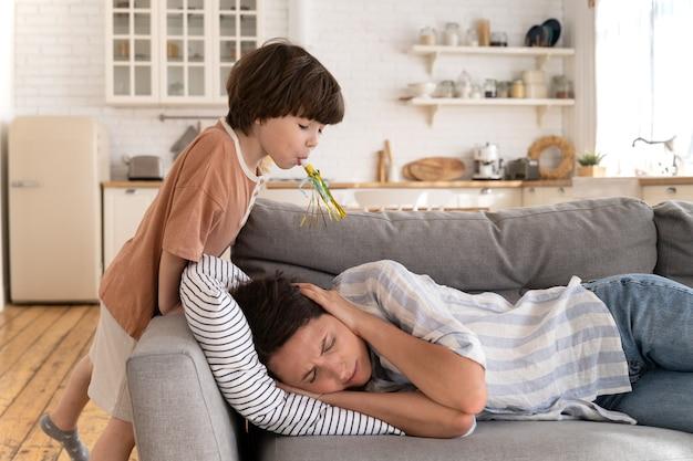 La madre single stanca copre le orecchie con la mano sdraiata e gli occhi chiusi si sente stressata da un bambino rumoroso e testardo