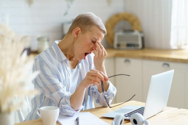 Donna di mezza età stanca e assonnata che si massaggia il naso e sbadiglia mentre lavora al laptop online da
