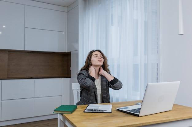 Donna stanca e assonnata che lavora su un laptop, a casa o in ufficio, lavora online