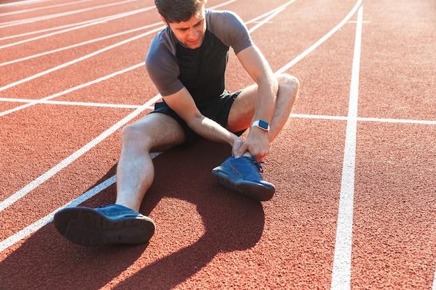 Sportivo stanco che soffre di un dolore alla caviglia
