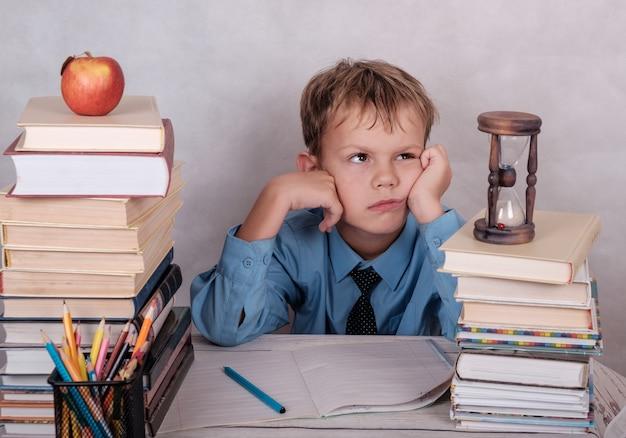 Stanco di studiare ragazzo europeo al tavolo con una montagna di libri, quaderni e matite.isolate