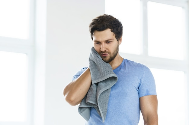 Uomo sudato stanco con un asciugamano dopo l'allenamento fitness in palestra