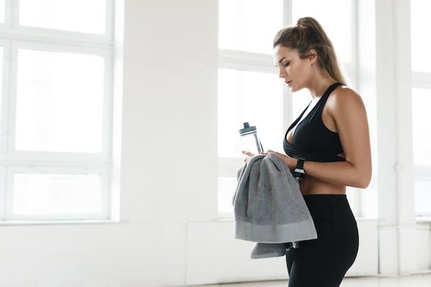 La donna sudata stanca beve acqua dopo un duro allenamento di fitness in palestra