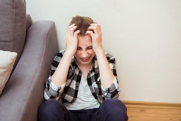 Ragazzo adolescente stanco che sente forte mal di testa, dolore emicranico, tenendo la testa. giovane infelice che soffre di depressione, ansia, attacco di panico, sistema nervoso e problemi di salute mentale