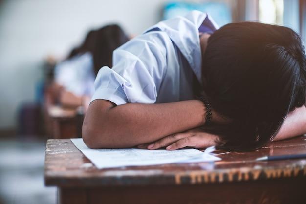 Studente stanco uniforme che dorme in un'aula di prova d'esame