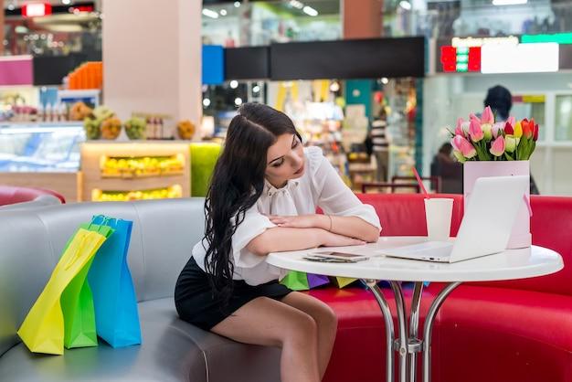 La donna stanca dopo lo shopping si è addormentata nella caffetteria