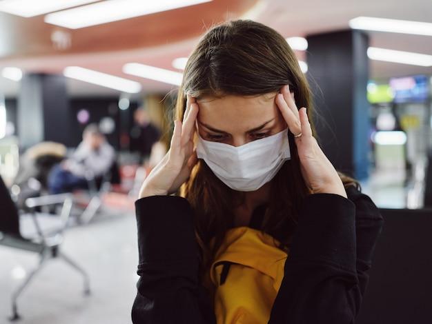 Donna stanca all'aeroporto che tiene la sua maschera medica alla testa in attesa