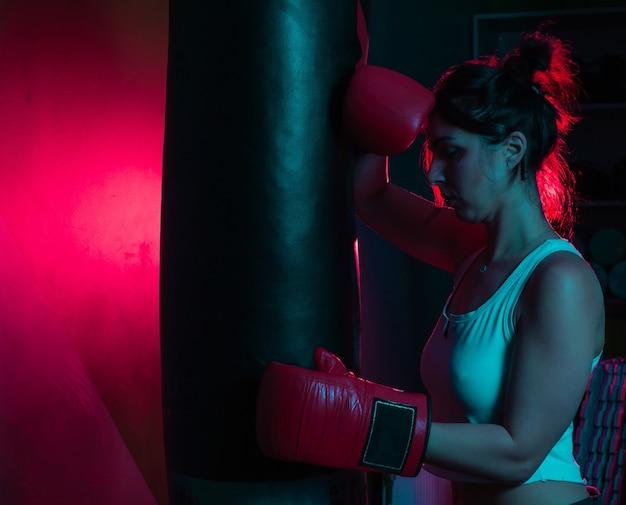 Boxer donna stanco in guantoni da boxe è appoggiato a un sacco da boxe in luce al neon blu rossa su sfondo scuro