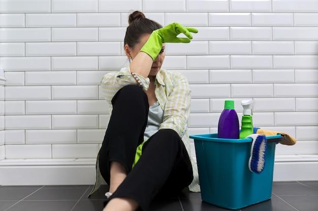 Donna stanca che fa le pulizie di casa in bagno femmina in guanti con detergenti, secchio seduto sul pavimento. fatica, stress, pulizia, casa