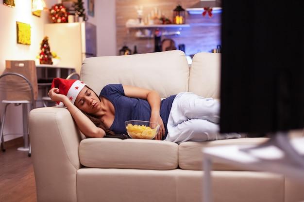 Donna stanca che si addormenta sul divano mentre guarda un film di natale in televisione