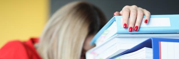 Donna stanca accanto a cartelle di documenti. scadenza sul concetto di lavoro