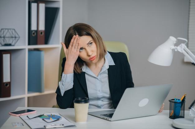 Donna stanca in vetri che si siedono al computer portatile mentre lavorando nell'ufficio
