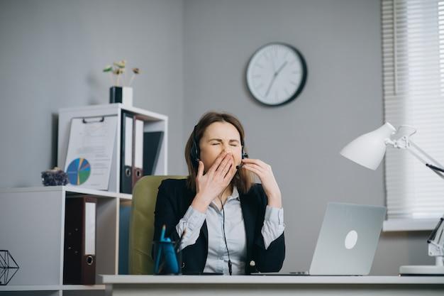 Donna stanca in cuffie che si siedono al computer portatile mentre lavorando nell'ufficio