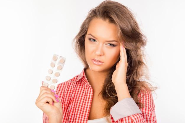 Donna stanca che tiene compresse e soffre di forte mal di testa