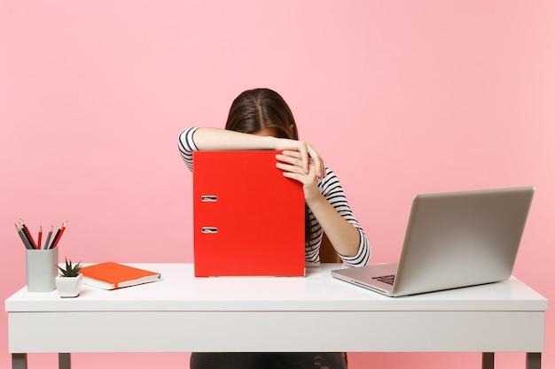 Donna stanca che si appoggia sulla cartella rossa con documenti cartacei e lavora al progetto mentre è seduta in ufficio con il computer portatile isolato su sfondo rosa pastello. concetto di carriera aziendale di successo. copia spazio.