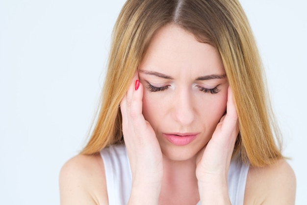 Donna stanca che massaggia le tempie sul muro bianco.