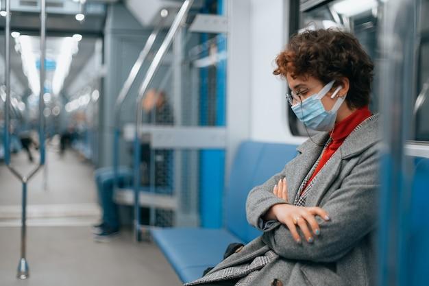 Una donna stanca con una maschera protettiva dorme in un vagone vuoto della metropolitana