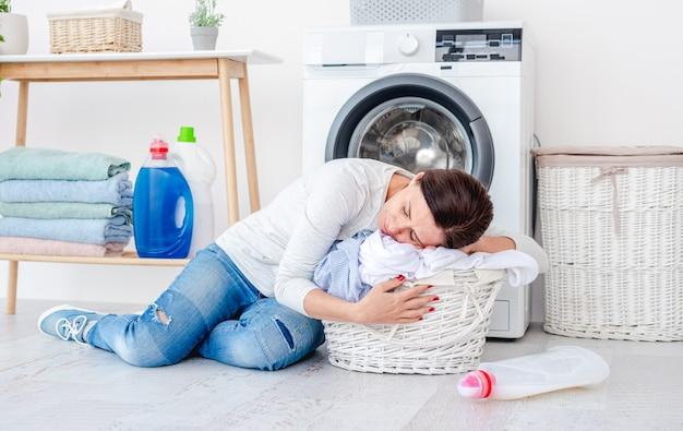 Donna stanca che riposa sul cesto della biancheria con vestiti freschi che si siede sul pavimento della stanza davanti alla lavatrice