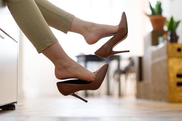 Donna stanca che riposa con i piedi che decollano marrone. affaticamento del piede