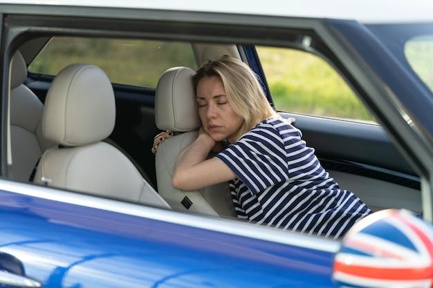 La donna stanca dorme all'interno dell'auto sul sedile del conducente la femmina adulta infelice si addormenta sul parcheggio dopo il lavoro