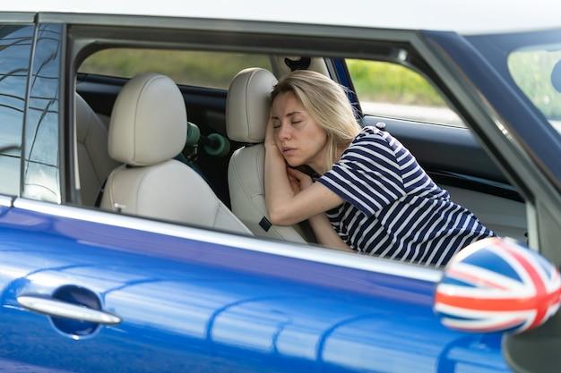 La donna stanca dorme all'interno dell'auto sul sedile del conducente la femmina adulta infelice si addormenta nel parcheggio dopo il lavoro