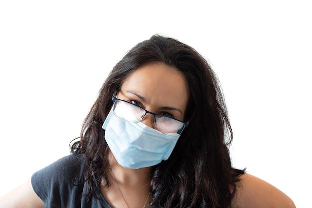 Donna stanca che indossa la maschera per il viso tshirt nera e occhiali appannati su sfondo bianco