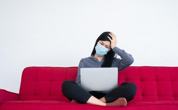 Donna stanca che indossa una maschera facciale, mal di testa ed emicrania, la sofferenza della sindrome dell'ufficio dopo lunghe ore di lavoro al computer. sindrome dell'ufficio e concetto di assistenza sanitaria.
