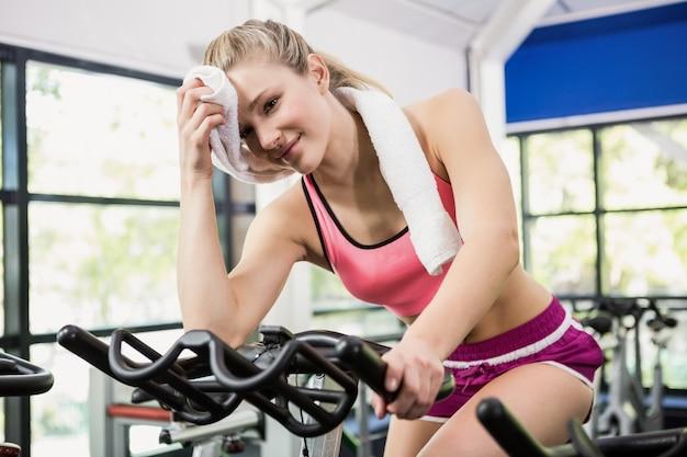 Donna stanca che pulisce il suo viso dopo l'allenamento