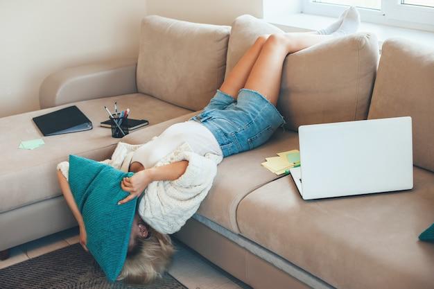 Donna stanca con capelli biondi sdraiata a letto a testa in giù facendo i compiti al computer portatile e utilizzando libri e documenti si copre il viso con un cuscino
