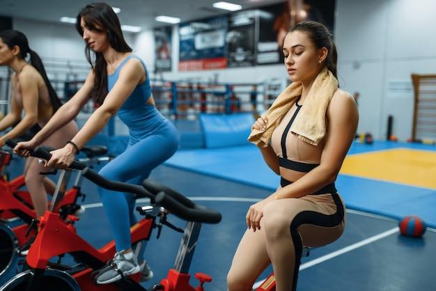 Donna faticosa con asciugamano su una cyclette in palestra