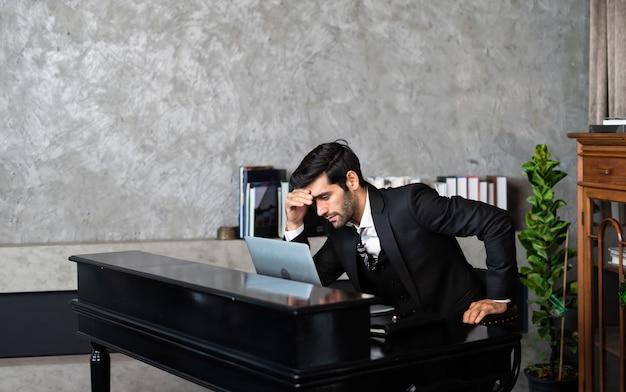 Uomo d'affari stanco e preoccupato sul posto di lavoro in ufficio tenendo la testa sulle mani dopo il lavoro a tarda notte. concetto di depressione.