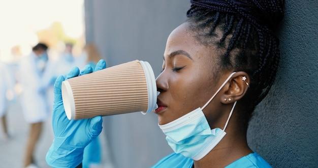 Stanco giovane donna afroamericana medico che toglie la mascherina medica e sorseggia una bevanda calda mentre riposa e si appoggia al muro con gli occhi chiusi. infermiera femminile graziosa che beve caffè e riposo dopo il duro lavoro