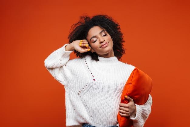 Stanco giovane donna africana che abbraccia un cuscino isolato sul muro rosso, gli occhi chiusi